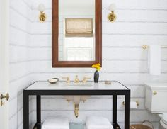 You can never go wrong with a powder room design by Nate Berkus Associates. We love the combination of the abstract black-and-white-print wallpaper combined with the gold accents and fixtures. The gold accents/fixtures are by themselves a statement that any additional decor would take away from this well-designed space.