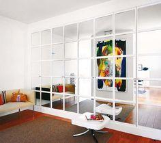 Un armario empotrado cubre una de las paredes del recibidor. Sus puertas con cuarterones de espejo crean la sensación de un gran ventanal y multiplican la luz.