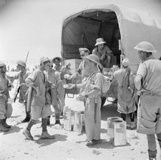BRITISH ARMY NORTH AFRICA 1942 (E 14620)   German and Italian prisoners captured during the advance on the Ruweisat Ridge receiving rations of 'bully beef', July 1942.