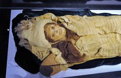 """This mummy (affectionately dubbed the """"Beauty of Xiaohe"""" by archaeologists), 1800 - 1500 BC has been preserved extremely well. She is so lifelike that she looks as if she's taking a nap. She has fair skin, round eyes, and a felt hat resembling an alpine head covering with a long feather stuck in the top."""