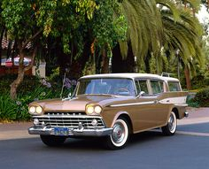 AUT 21 RK1397 03 © Kimball Stock 1959 AMC Rambler Custom Cross Country Wagon Gold And White 3/4 Front View On Pavement By Trees