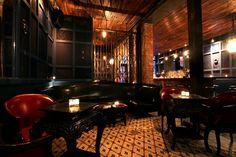 Madam Geneva's speakeasy- dark wood, geometric floor, dark cherry colors, wood, candles