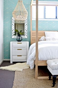We finished our Boho beachy bedroom makeover! With a gorgeous French Oak four-poster bed, all-white bedding, turquoise Shibori wallpaper and wooden beaded chandelier, it's like a holiday at home! Click through for pics!