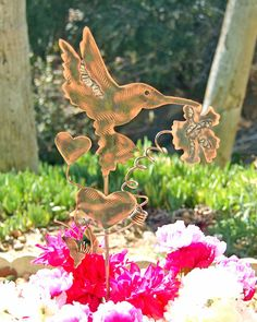 Hummingbird outdoor sculpture copper metal garden yard art plant stake by Garden Copper Art is created with artistic twisted solid copper wire wrapping, and an artist touch of artistic free flowing melted soldered applied to wings and flower. This unique hummingbird is accented with a