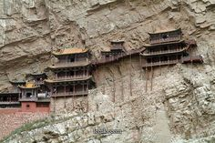 "Mt. Huashan, Xian, China. XUANKONG SI – ""The Hanging Monastery"" – has stood the test of 1,400 years, and earthquakes no less. The halls and pavilions of this structure follow the contours of the rock face, its buildings connected by bridges and walkways, the highest of which wavers over 200 ft above the riverbed atop stilt-like pillars."