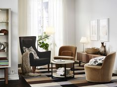 A living room furnished with two easy chairs that swivels, covered with dark beige velvet. Combined with a black high-back armchair and a small round coffee table.