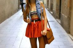 denim vest with bandeau top, high waisted skirt, and long ivory tooth necklace.