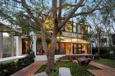 """O projeto do arquiteto Javier Muñoz Menéndez implantou a casa """"Entre Árboles"""" de forma a acomodar as 52 árvores existentes no terreno. Decks feitos de madeira tropical compõem os caminhos pelo jardim da residência localizada em Yucatán, no México"""