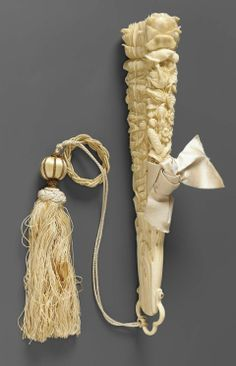 Carved ivory wedding fan, Swiss, 1877 Carved Ivory Wedding Fan With Thin Flat Sticks, Two Outside Sticks Are Thick And Heavy Carved In High Relief Design O Roses, Lilies, Etc., Silk And Gold Tassel Attached To Ring At Bottom - Switzerland c.1877 - Museum Fine Arts-Boston