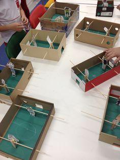 Jogo de pebolim ou totó feito com caixas de sapatos, pregador e palito de churrasco