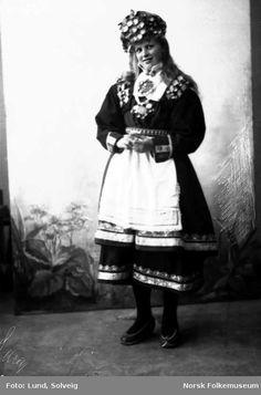 Digitalt Museum - Studiofotografi av kvinne med brudedrakt og brudehatt/krone på hodet. Stående foran malt bakgrunn med blomster. Helfigur Frontalt vendt. Ser ut av bildet.