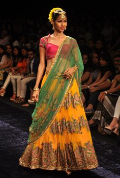 Yellow lehena with patchwork and a pink blouse with a green dupatta.