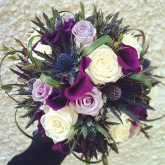 Another stunning example of how the dark purple of scottish thistle can compliment the white roses and greenery in this bouquet.