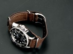Rolex Submariner with a vintage style nato brown leather strap.