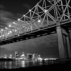 Black and white picture of the New Orleans Skyline at night and the Ponchartrain Expressway Bridge.