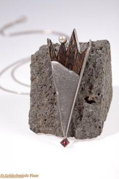 Lange Silberkette die spitz zuläuft. Am unterern Ende strahlt ein in Gold (585) gefasster rosa Turmalin im Carre-Schliff. Im oberen Bereich bildet ein