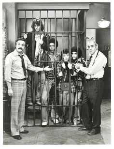 """Hal Linden & Abe Vigoda of Barney Miller (1975-82) lock up """"The Sweathogs"""" of Welcome Back, Kotter (1975-79): (left to right) John Travolta, Lawrence Hilton-Jacobs, Ron Palillo & Robert Hegyes. This sitcom-crossover was solely a publicity photo for ABC's Thursday night line-up, the casts never appeared together in an actual episode."""