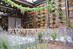 Wedding decor by Greenery NYC. Planted Aisle runners of Piglet Grass and Russian Sage, Fern Garland, and Cafe Lights at the Brooklyn Winery