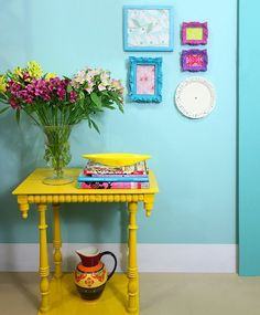 I adore this....yellow table, turquoise walls, colorful art!