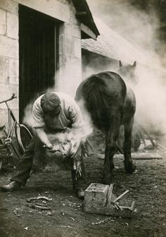 A farmer buring the hoof of a horse before shoeing it in Scotland, May 1921. Photograph by William Reid, National Geographic.