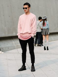 Baby pink sweater with black cropped trousers and all-black trainers to create a summer sports luxe style