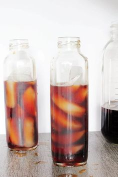 two tall, squarish bottles of strong iced tea filled with ice cubes and iced tea