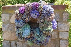 My favorite flowers in a wreath hung on an outdoor stone fireplace.