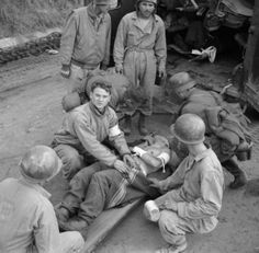 US Army and captured German medics attend to a wounded German soldier at Anzio, Italy, 6 February 1944.
