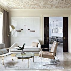 Even in the most neutral of spaces, a wallpapered ceiling can make a big statement. In this cream living room, wallpaper takes this space from dull to stunning. An agate wallpaper pattern in shades of white adds warm texture above.
