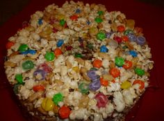 Yum... Id Pinch That! | Pop Corn Cake  Ingredients are: M & M's, Spiced Gum Drops, Peanuts, Marshmellows, and pop corn.  Hope you enjoy it.