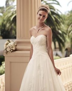 Strapless sweetheart neckline with Soft Tulle ruched bodice. The skirt is a gathered A-line silhouette. The Soft Tulle overlay features non-beaded lace ...
