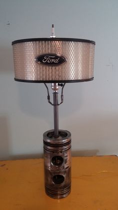 Table lamp crafted from truck pistons with air filter shade