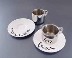 Anamorphic Cups: the first product to employ the centuries old visual play of the anamorphic cylinder. The stainless steel cup has a polished mirror finish. The porcelain saucer is printed with distorted images or words. These graphics can only be viewed correctly though the curved, reflective surface of the cup.