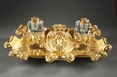 Grand encrier en bronze doré de forme chantournée, composé de deux réceptacles en verre taillé et leurs bouchons pour l'encre décorés de corolles de fleurs et un godet central...