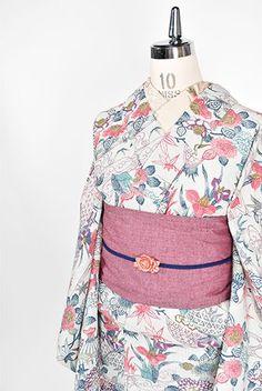 細やかな十字が織りだされた絣織りの風情をだしたかのような白の地に、優しい色どりとタッチで染め出された茶屋辻風の四季の草花風景模様が美しいウールの単着物です。