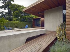concrete and wood. clean hedge lines. textured, spiky plants in forefront.