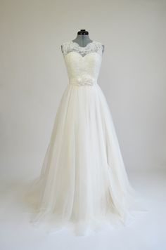 Ivory sleeveless lace wedding dress with tulle skirts.