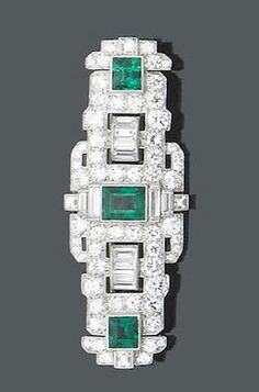 An art deco emerald and diamond panel brooch, circa 1930 Set with three step-cut emeralds upon a pierced buckle panel of geometric design set throughout with brilliant and baguette-cut diamonds, diamonds approx. 2.90ct. total, length 5.5cm.