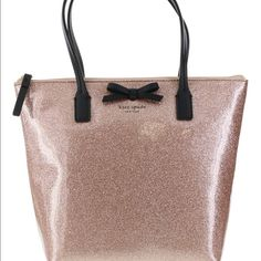 """Kate Spade Mavis street Jeralyn tote and dust bag Wrapped in rose gold pink sparkled PVC with golden tone hardware. This Kate Spade tote is lined in coordinating Capital Kate logo print fabric and features an open slip pocket. It has a fully zippered top closure and the front is accented with Kate Spade's iconic logo bow. There are dual handles with a drop of about 6"""". It measures 8.5"""" (L) at the bottom and tapers to 12"""" (L) at the top x 9.5"""" (H) x 3"""" (W). kate spade Bags Totes"""