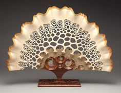 """Mark Doolittle: """"Sea Fan"""" (17""""h x 20""""w x 6""""d). Basswood fan with Amboyna Burl center and Bubinga base. Contains five inlayed fossil ammonites. George Post, photography."""