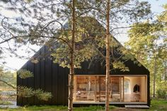 Nestled into a clearing in a forest of tall pines in the Stockholm archipelago, the exterior of this island home is clad entirely in folded black sheet metal. Three glazed sliding doors with hardwood frames provide entrances and direct access to the outdoor areas.