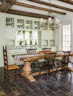 For the ultimate farmhouse-style breakfast room, this homeowner mixed a hefty trestle-base table with antique ladder-back and Windsor chairs and a polished nickel chandelier that evokes equestrian tack supply. The cabinets are painted a light shade of green to contrast the darker floors.   - CountryLiving.com