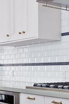 Subway tile with navy penny round stripes.  Globe and Mail Real Potential Navy White Kitchen Backsplash