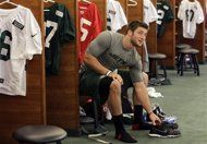 New York Jets quarterback Tim Tebow sits at his locker at the teams football training facility, Thursday, May 10, 2012 in Florham Park, N.J. (AP Photo/Julio Cortez)