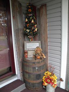Primitive decor. Love my front door area. Barrel, sunflowers, scarecrow fall 2012