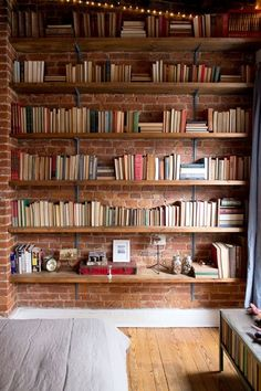 This exposed brick wall behind these book shelves adds a sophisticated yet cozy touch.    Let www.bricktilesnationwide.co.uk help you out with your dream home!