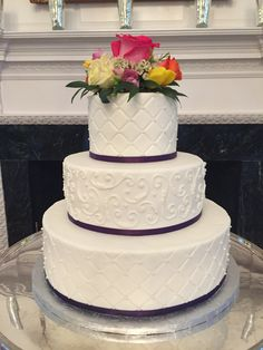 3 tier round white buttercream wedding cake with scrollwork and fresh flowers