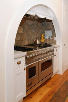 Raw stone in a New York cottage. Stone helps set off this cooking nook from the rest of the clean, white kitchen in this Long Island home. Tucked under a curved enclosure — part of the home's original front door — it looks almost like a cozy cave to cook in.