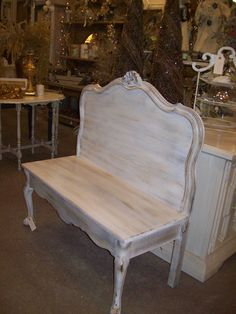 old bed repurposed into a bench looks like an old headboard and poss a coffee table with one side cut off