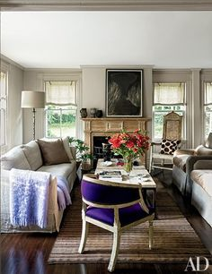 A painting by Beverly Pepper overlooks the living room, which features a sofa, cocktail table, and floor lamp from Lucca Antiques; a Loro Piana fabric covers the chair in the foreground, and the patterned pillow is by Madeline Weinrib.